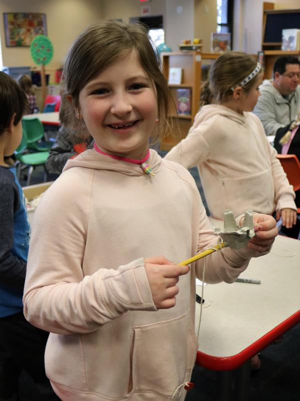 2nd grader shows off 18th-century style toy she made during Colonial Days at Wilson.
