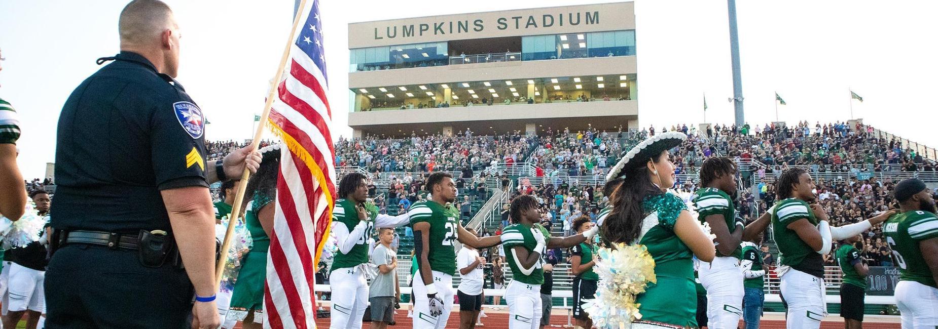 crowd at football stadium singing national anthem