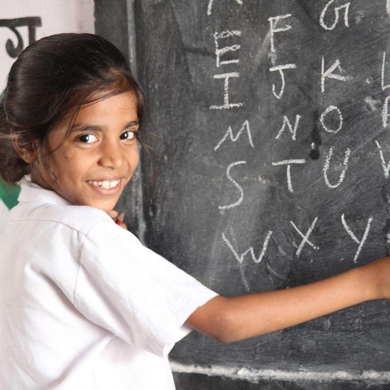 Girl at school writing alphabet letters on chalkboard