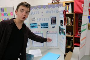 Student standing in front of science project
