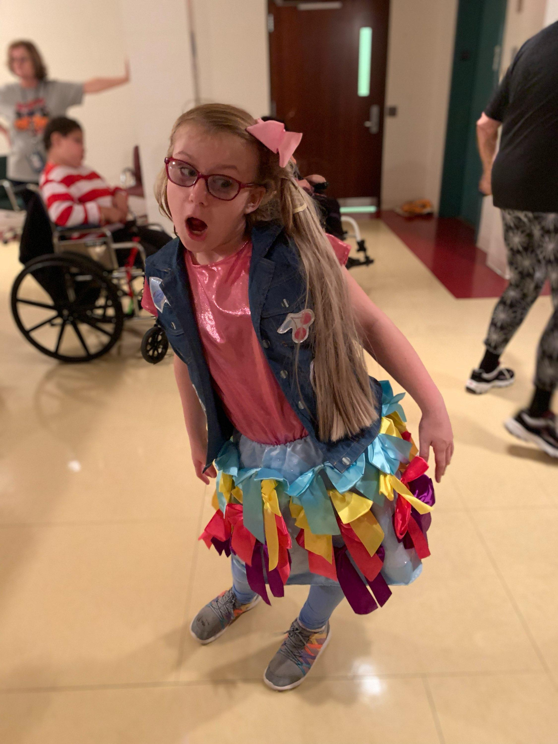 Student dressed up in a jean jacket and skirt with brightly colored ribbons