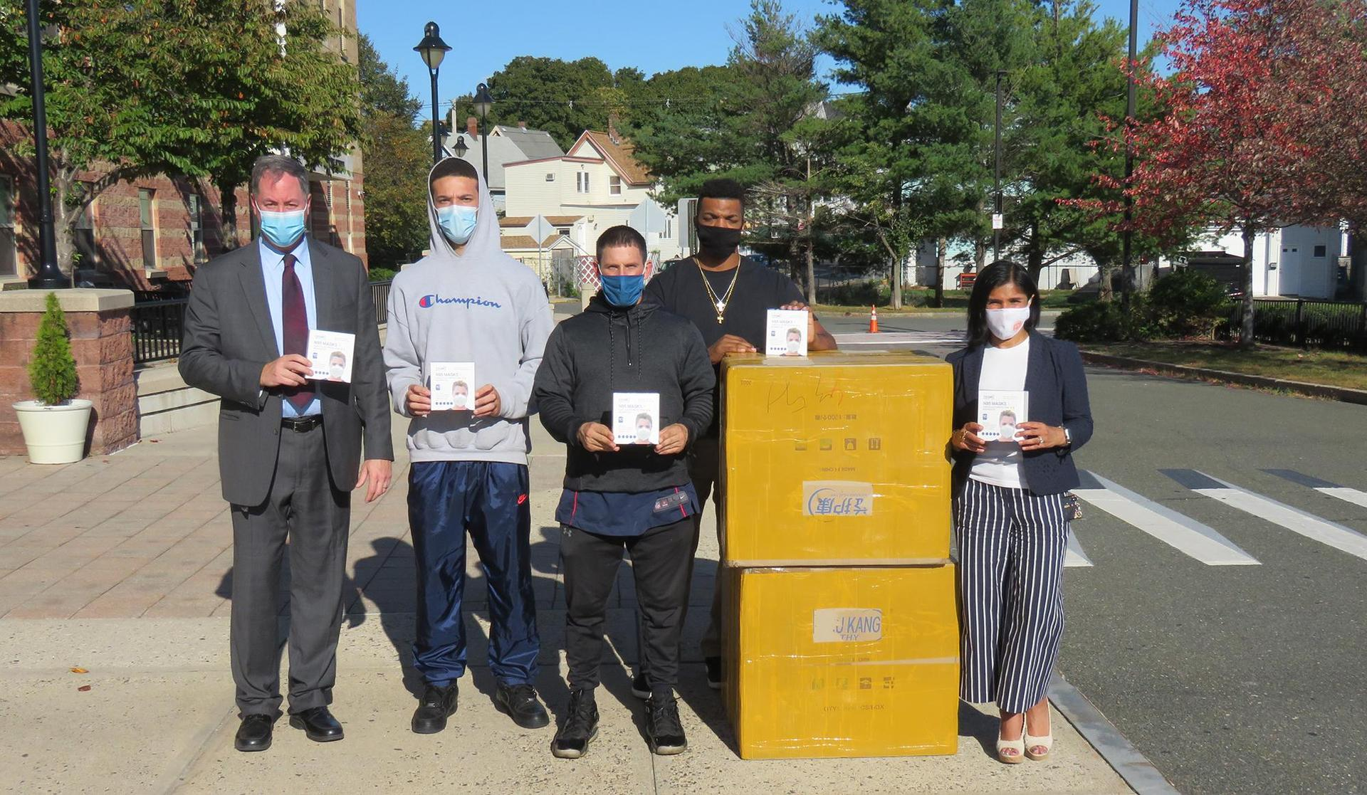 Posed photo, administrators and staff standing with a box of donated masks