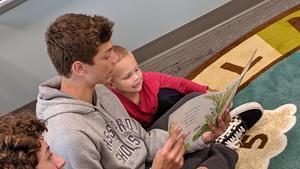 A Hopkins freshman reads to an Otsego preschooler