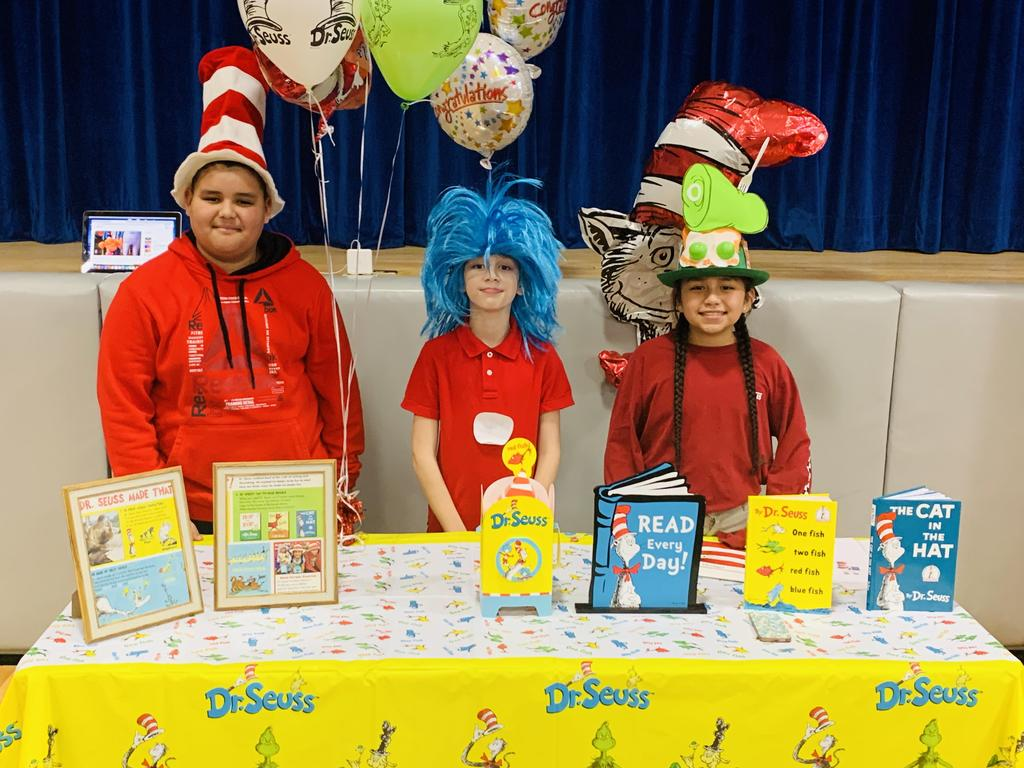 Three students at a table with Dr. Seuss books s