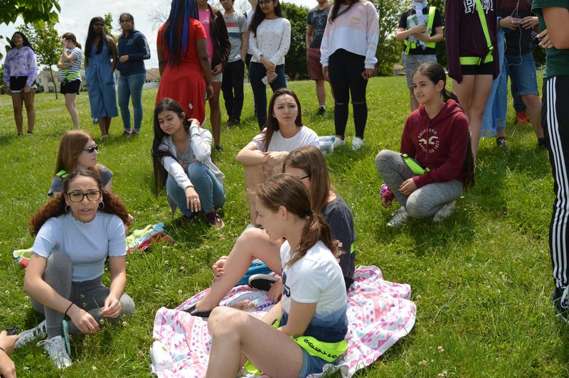 7 girls (three 6th graders and three 0th graders) are sitting on the grass. A group are standing behind waiting to meet their buddies