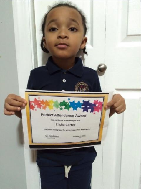 Elisha Carter holding perfect attendance certificate