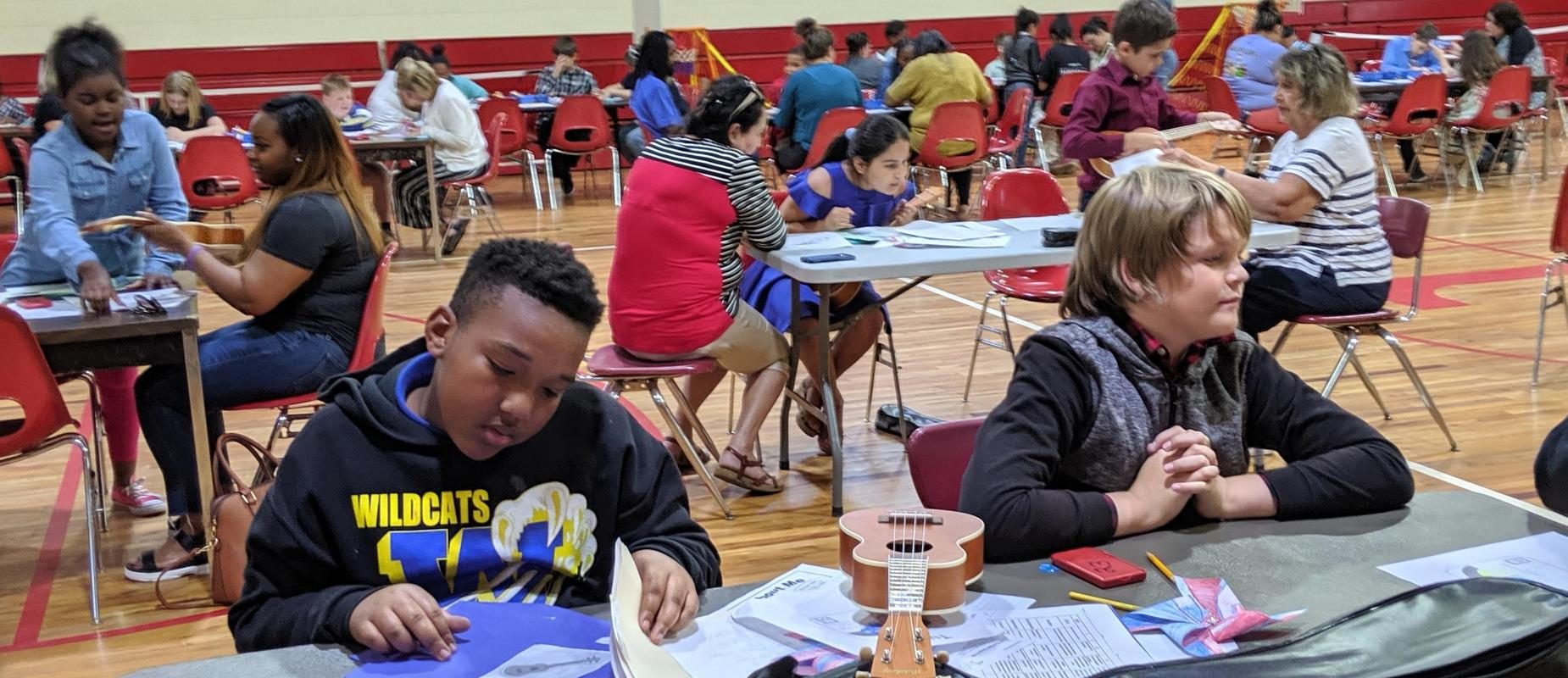students in gym at tables doing music activities with parents
