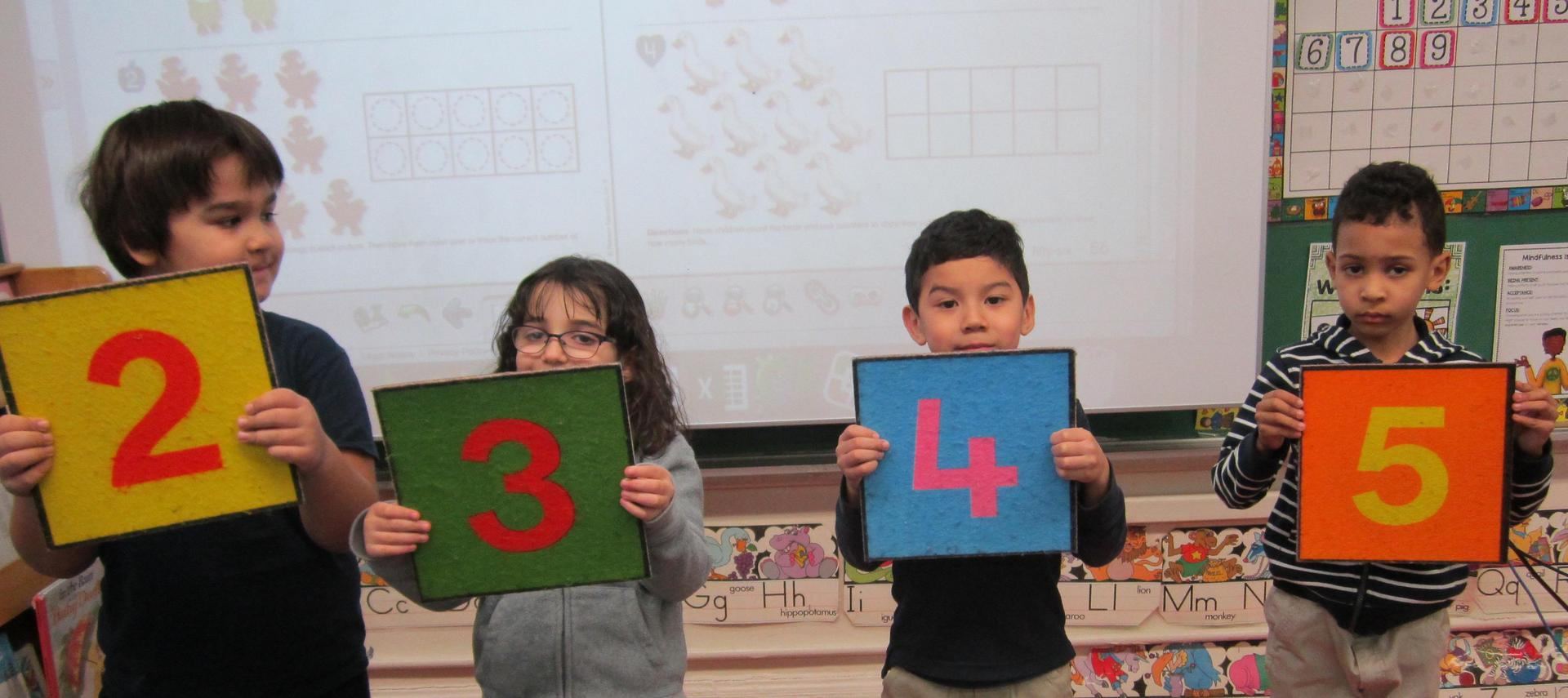 kids holding numbers 3 & 4