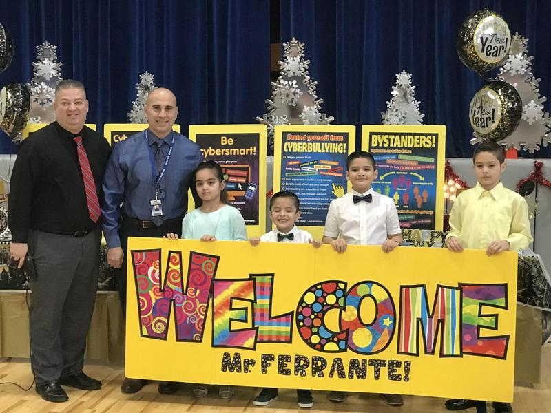 Principal Rivera and new Asst. Principal Ferrante with welcome banner and kids