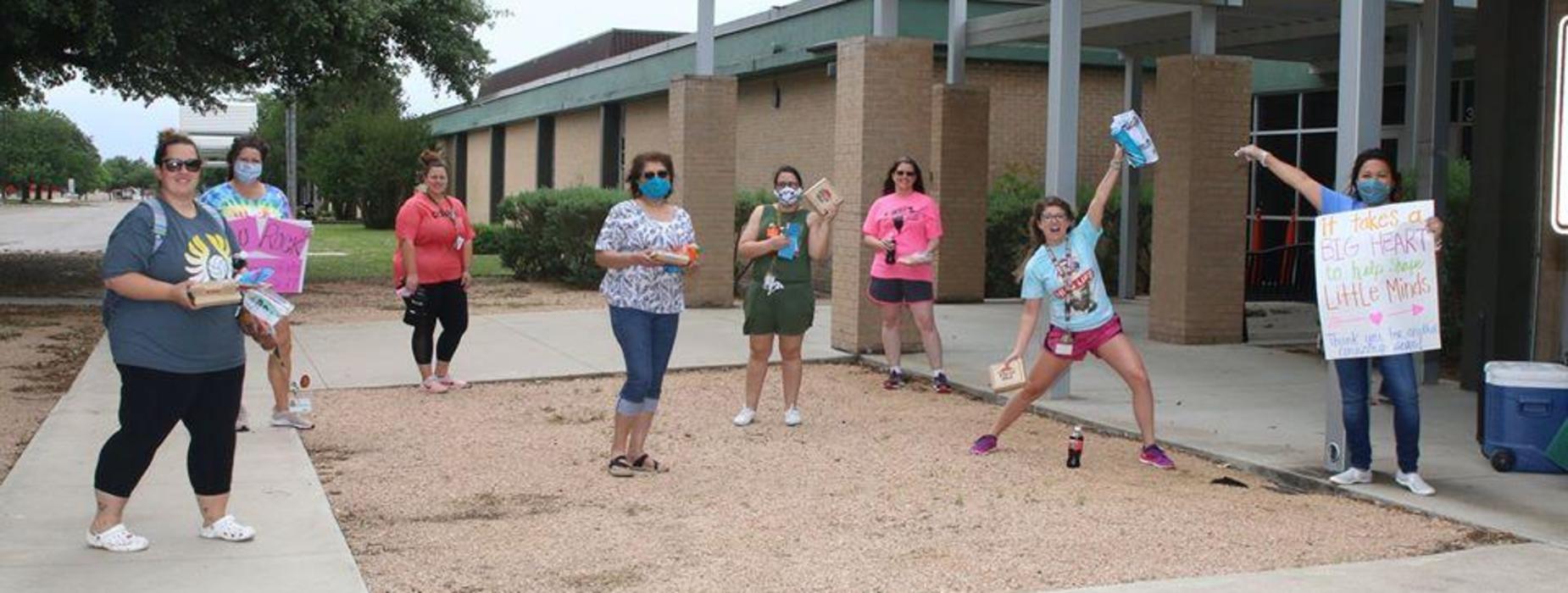 Teachers in front of school.