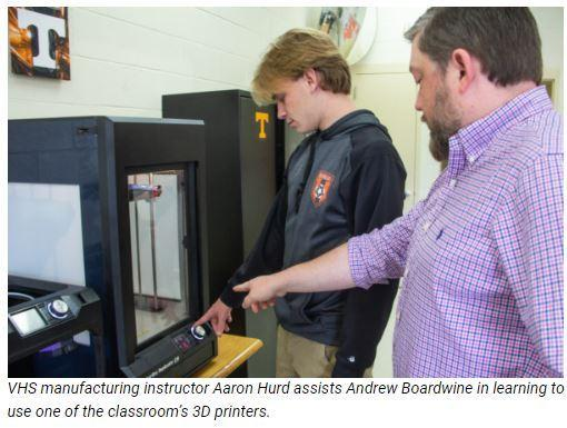 VHS manufacturing instructor Aaron Hurd assists Andrew Boardwine in learning to use one of the classroom's 3D printers.