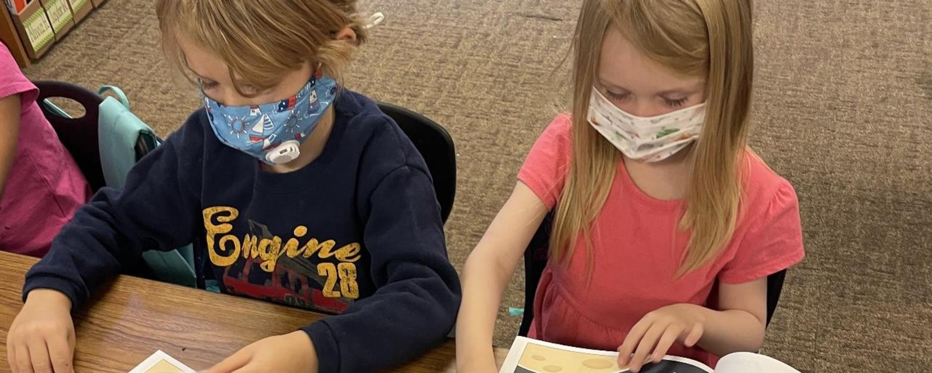 Students reading books about space.