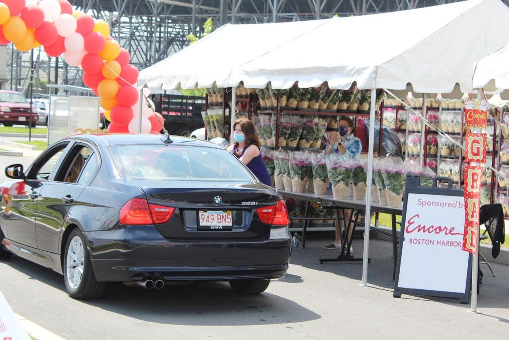 Car approaching balloon arch, stacks of flowers