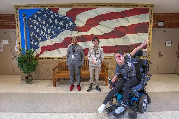 Students in front of a flag mural