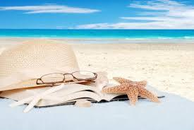 photo of books, shells and starfish on a beach