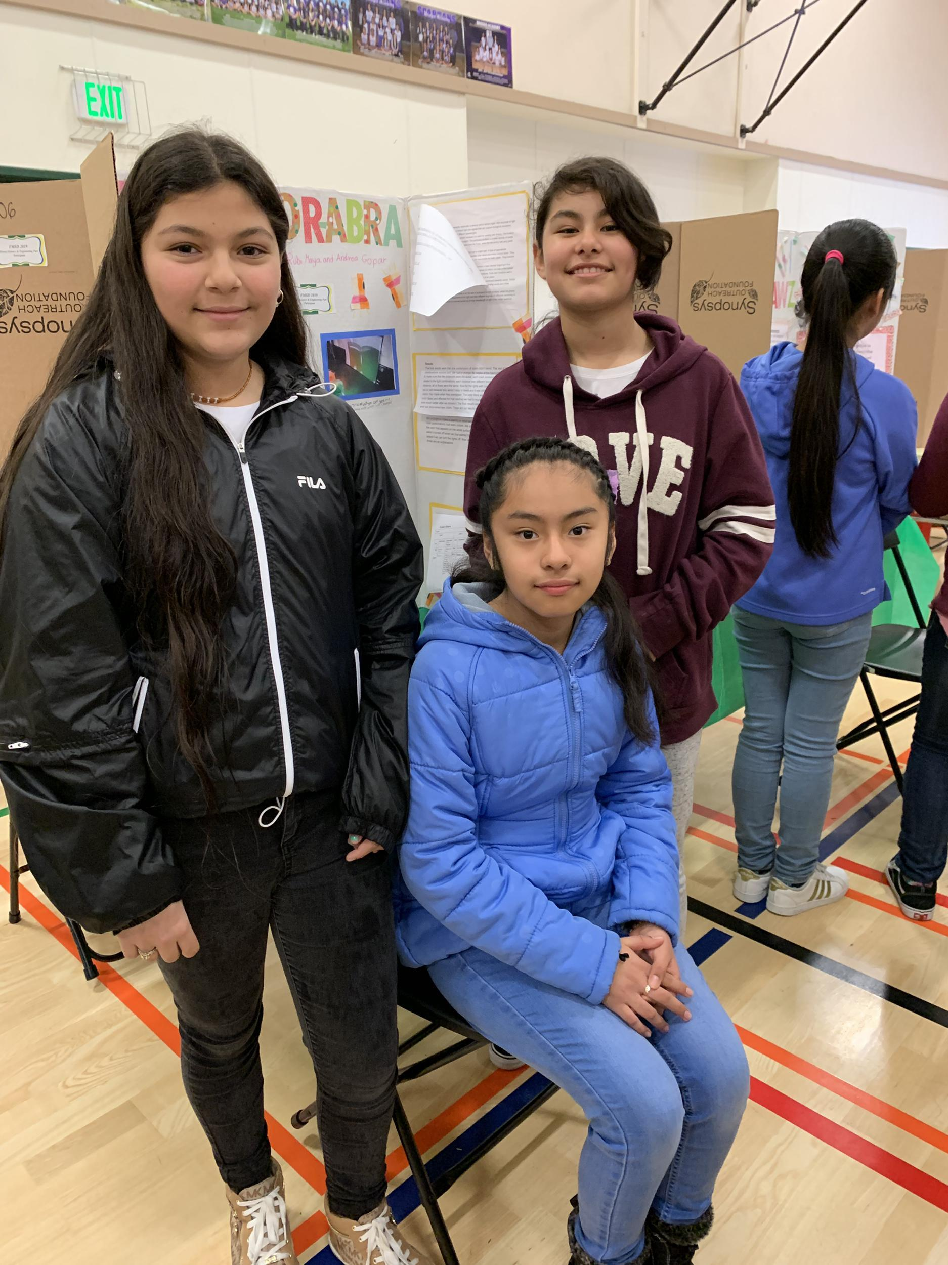 Students sitting, waiting for their science fair projects to be judged