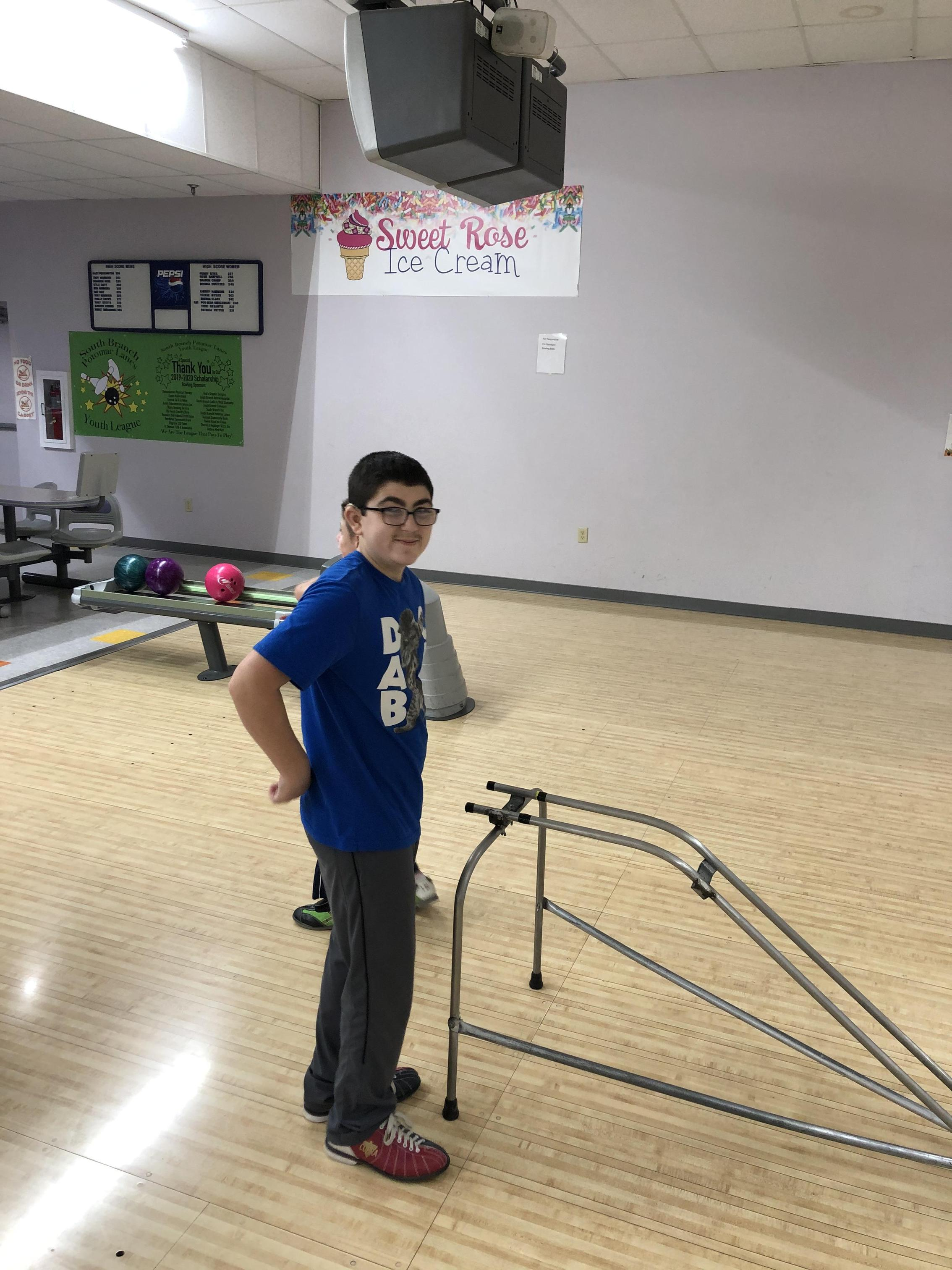 Student standing by a Bowling Ball Ramp to take his shot