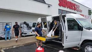 People loading van with collected items