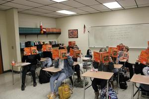 Students in classroom with books covering faces