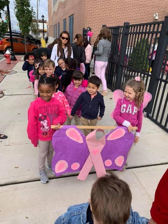 two girls leading their class with a purple butterfly banner