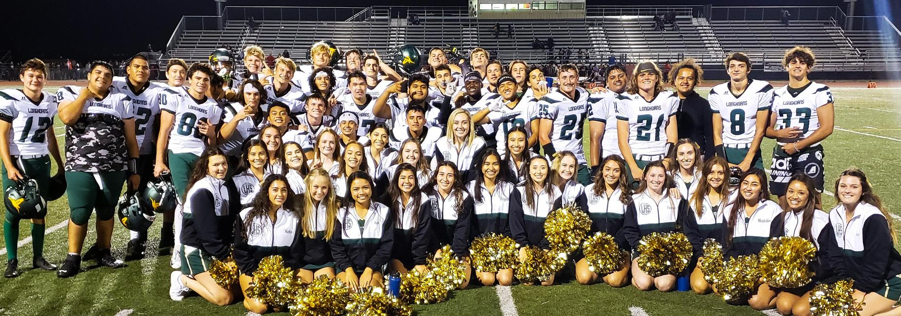 Football team and cheerleaders posing on the field after the first game of the 2019 season