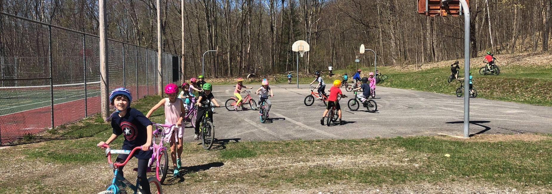 children riding bicycles on blacktop