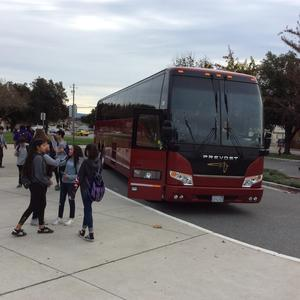 students at Bridges Academy getting off and standing next to a red tour bus