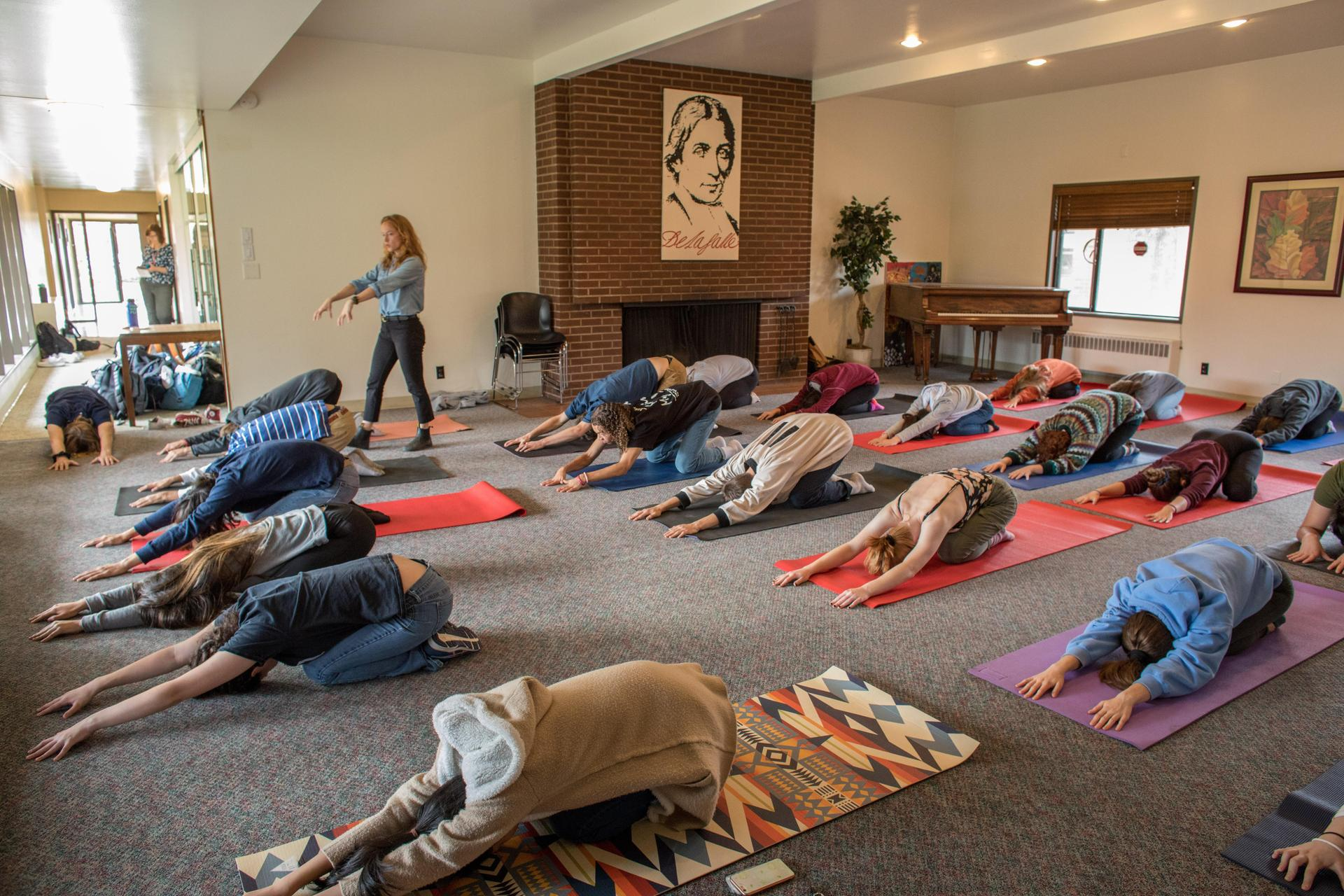 teacher directing a yoga class