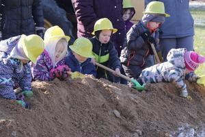 preschoolers dig in the dirt for the groundbreaking.