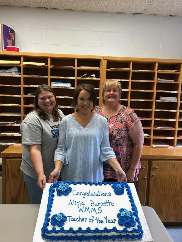 Mrs Ray, Mrs Burnette and Dr Gardner holding cake.