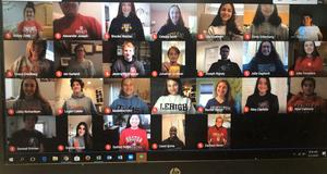 Photo of screenshot of students on computer screen wearing college gear for a virtual College Decision Day.
