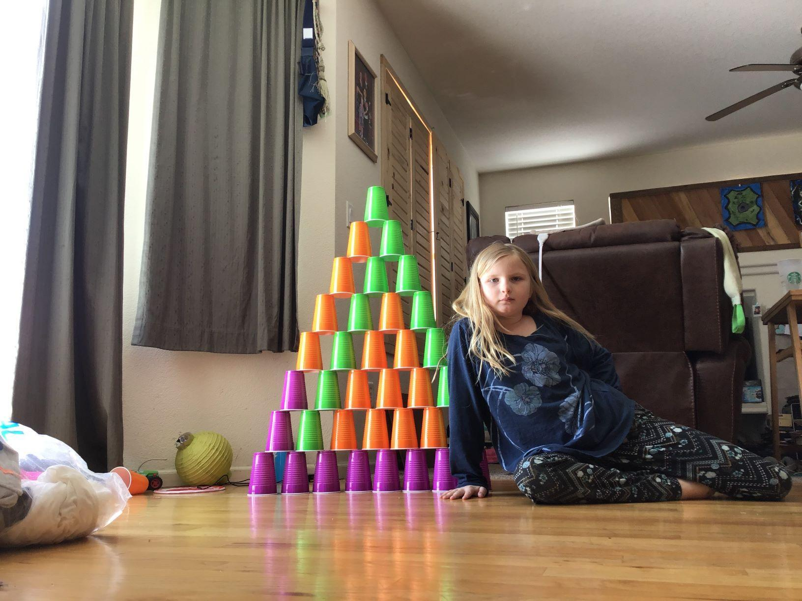 student at home behind pyramid of stacked cups
