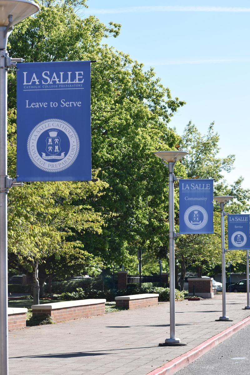 blue school flags flying over sidewalk