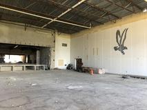 Demolition complete in the gym, the stage, walls and floor are bare.