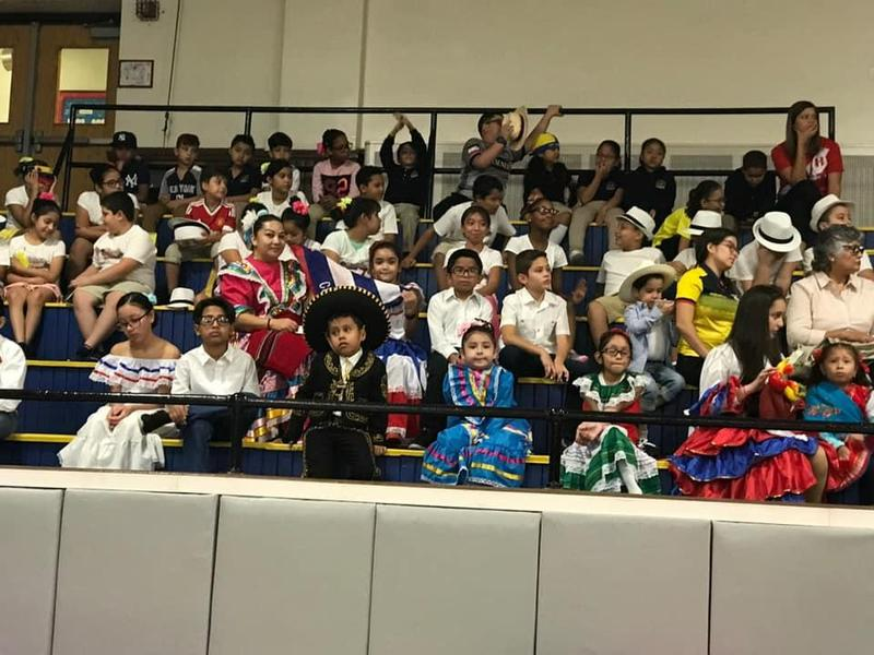 many children dressed in hispanic costumes waiting to perform