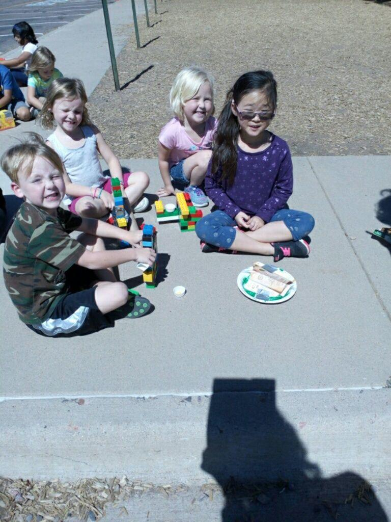 Kindergarteners use the engineering design process to create a structure that minimizes the sun's effect on their melting chocolates.