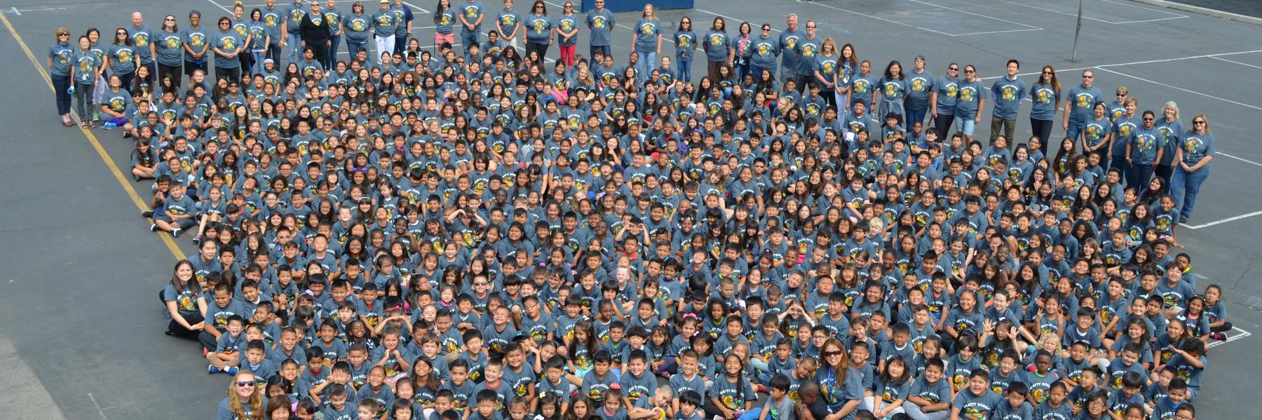 Students and staff gather together on the playground for an aerial view photo opportunity in their 2017-18 reading t-shirts.