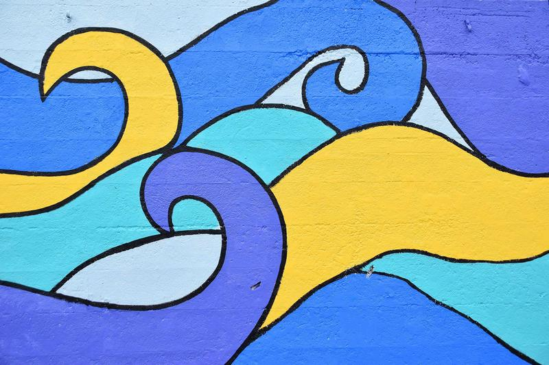 A close up of a mural on a long wall, wave design in blues and yellow