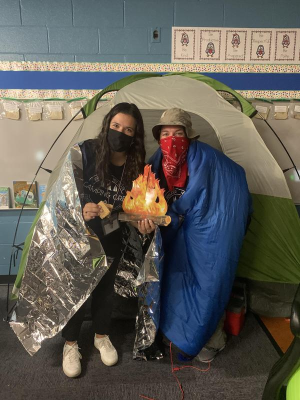 Two teachers pose for a picture in front of a tent for a class campout