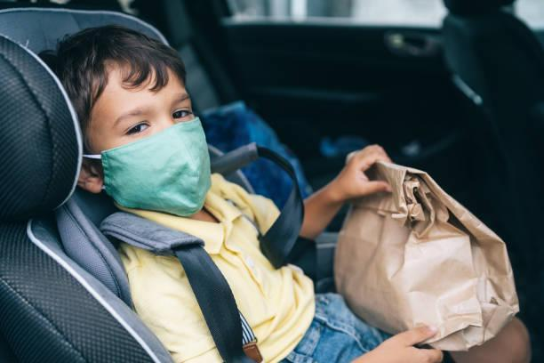 Boy buckled up in car seat, wearing a mask, holding a paper sack