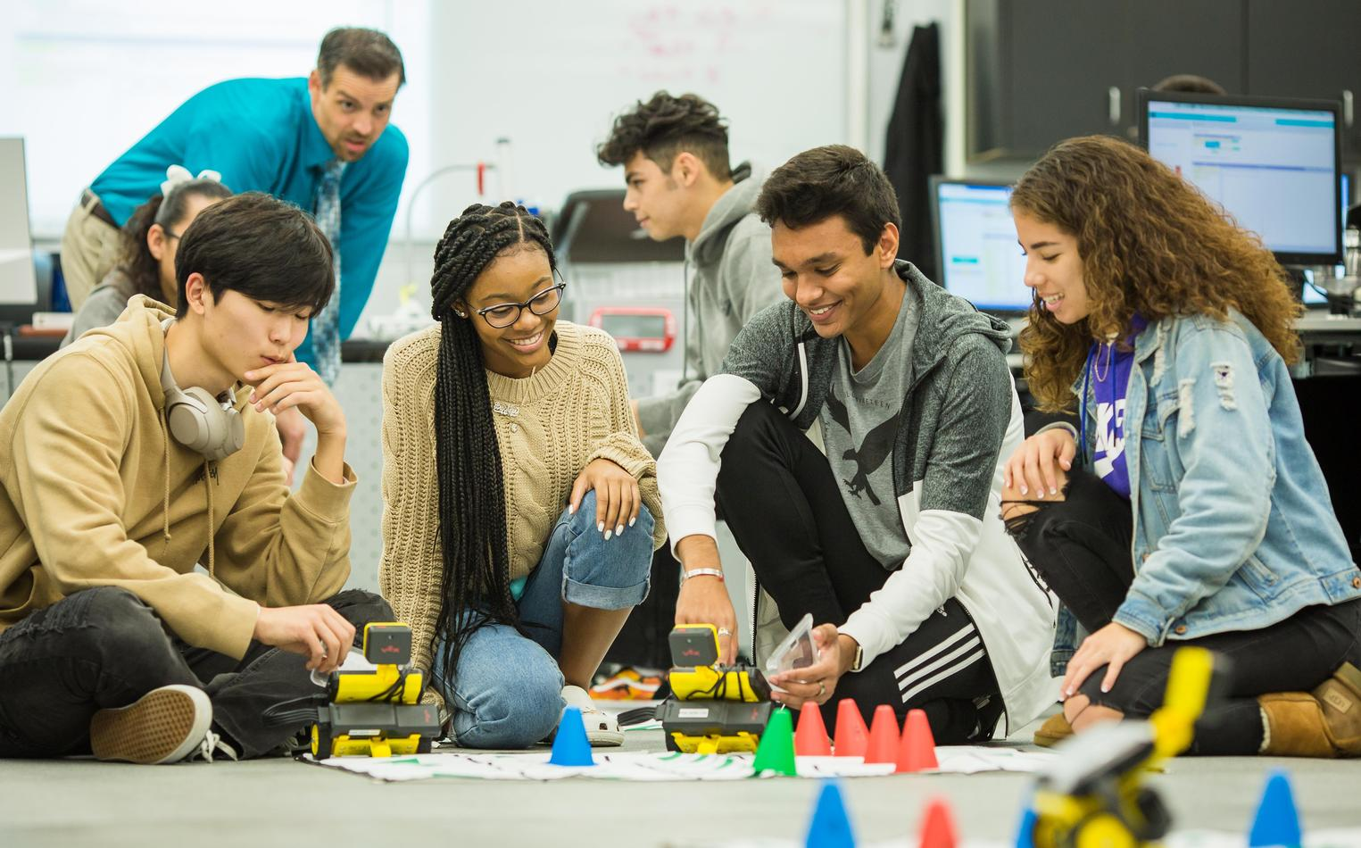 A group of students explore using remote controlled robots.