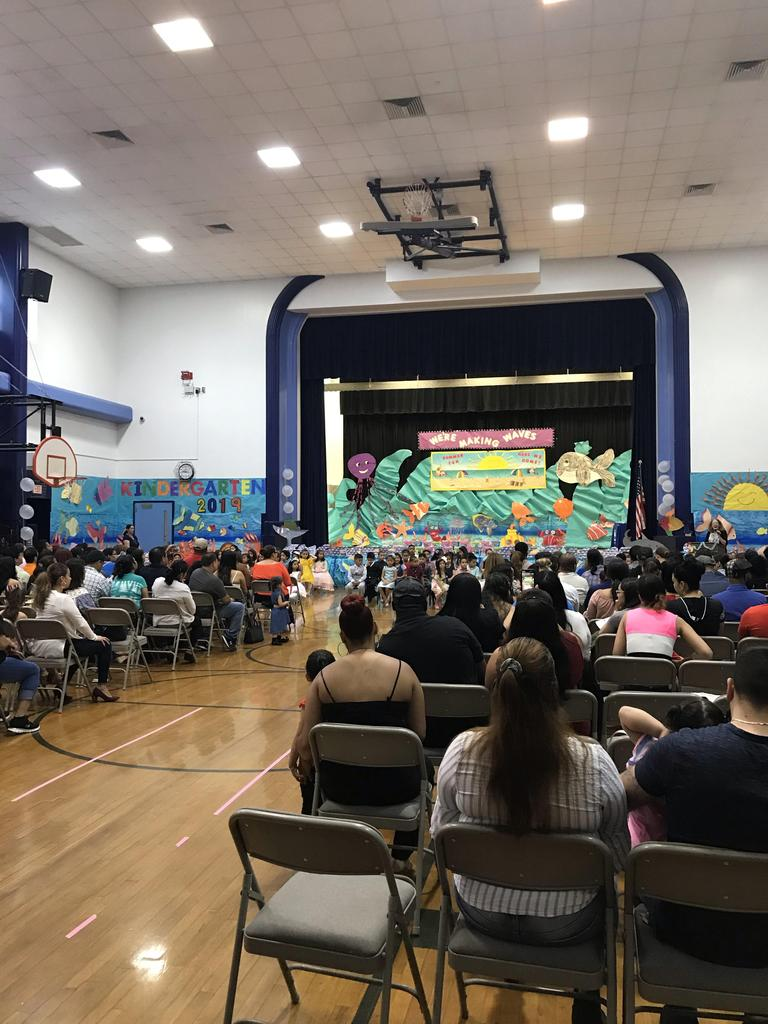 view of the parents in the audience and the children performing in front of the stage with the gym decorated as under the sea