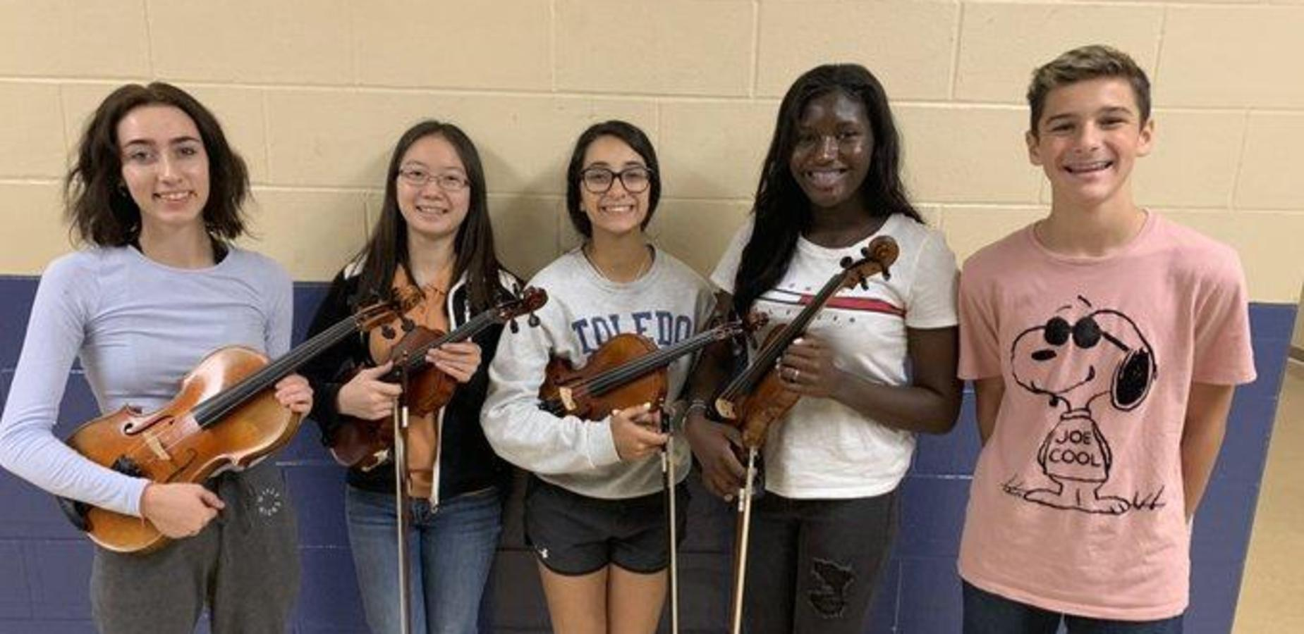 This is a photo of students in the Southwest Region Orchestra representing Fairfield High School. They are holding their violins and violas.