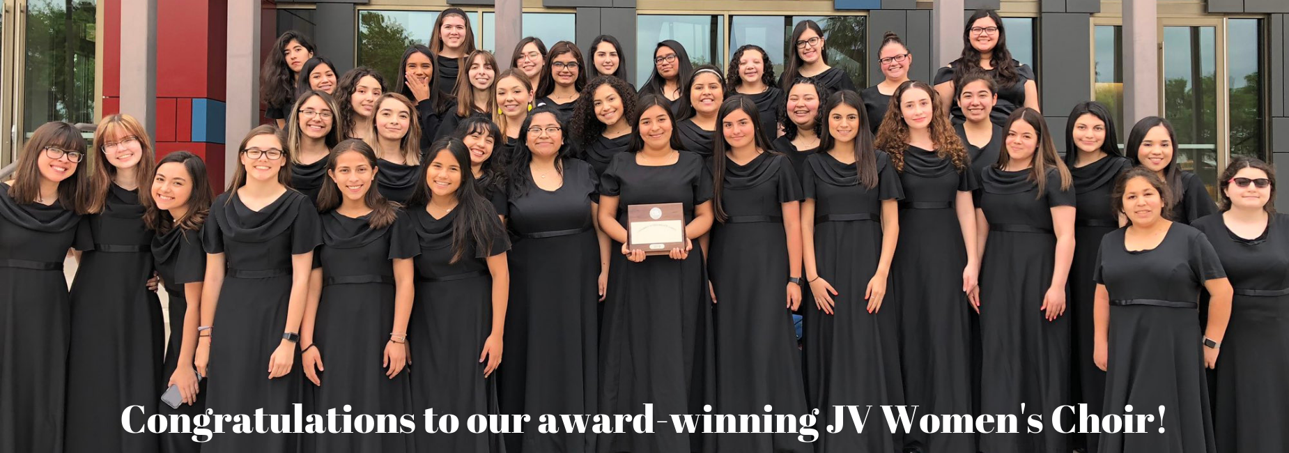 Ladies in gowns standing with gold award from UIL Choir competition