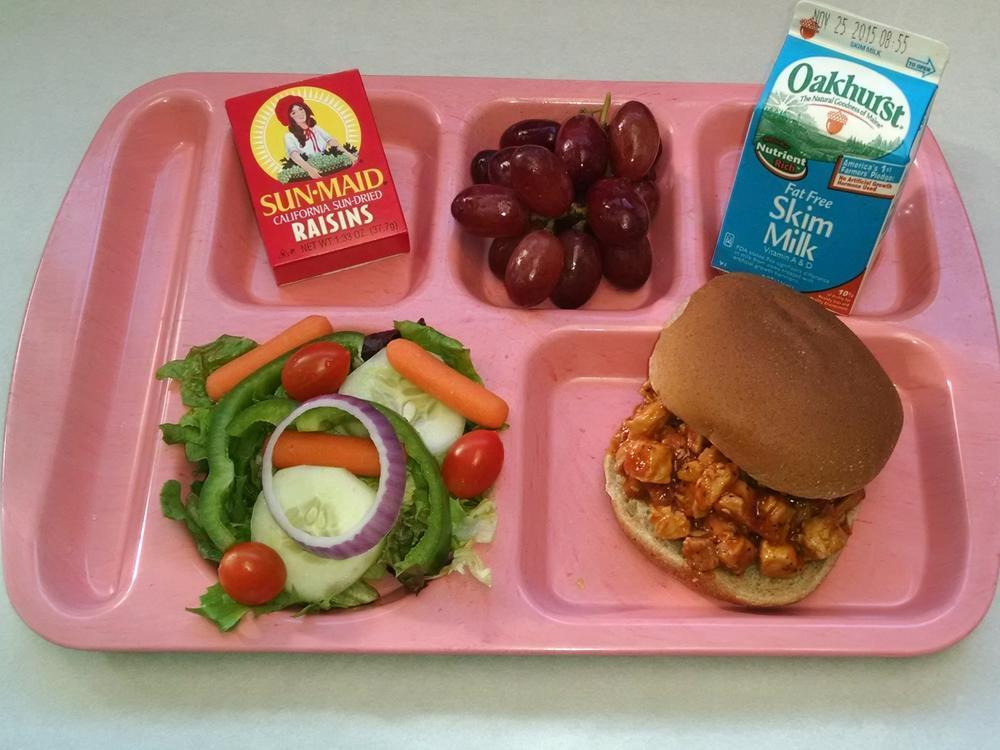 BBQ Chicken on a Bun with Salad, Grapes, Raisins and Milk