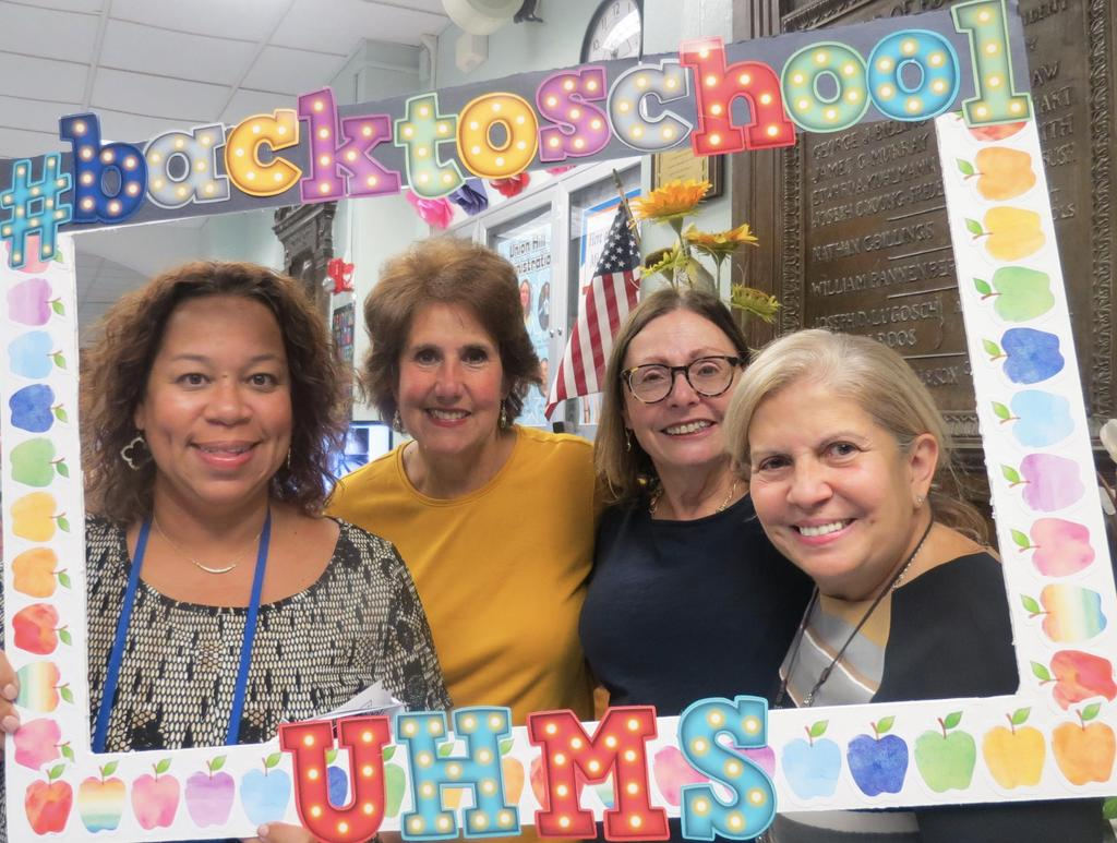 Ms. Garcia, Ms. Capizzi, Mrs. Dickson, and Ms. Valle in the front entryway with a back to school photo board