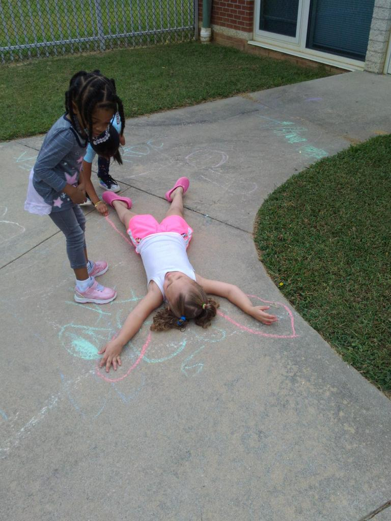 Pre-K students tracing themselves with chalk on the sidewalk