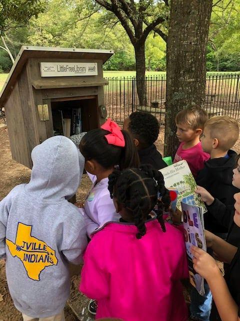 students stocking a free library
