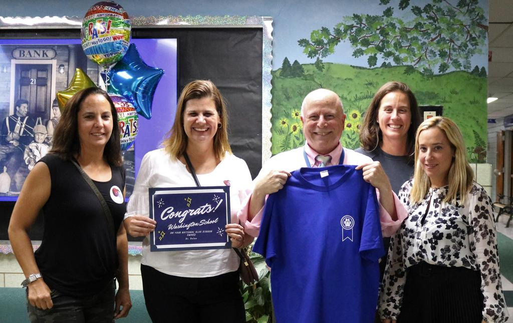 Photo of Washington School principal Dr. Andrew Perry holds National Blue Ribbon School shirt with members of PTO,as the school is announced a Blue Ribbon school.