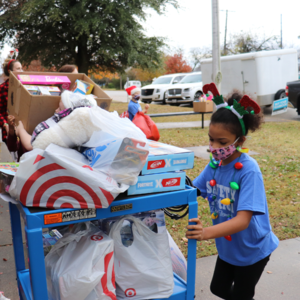 dyer students rolls cart of toys inside the school